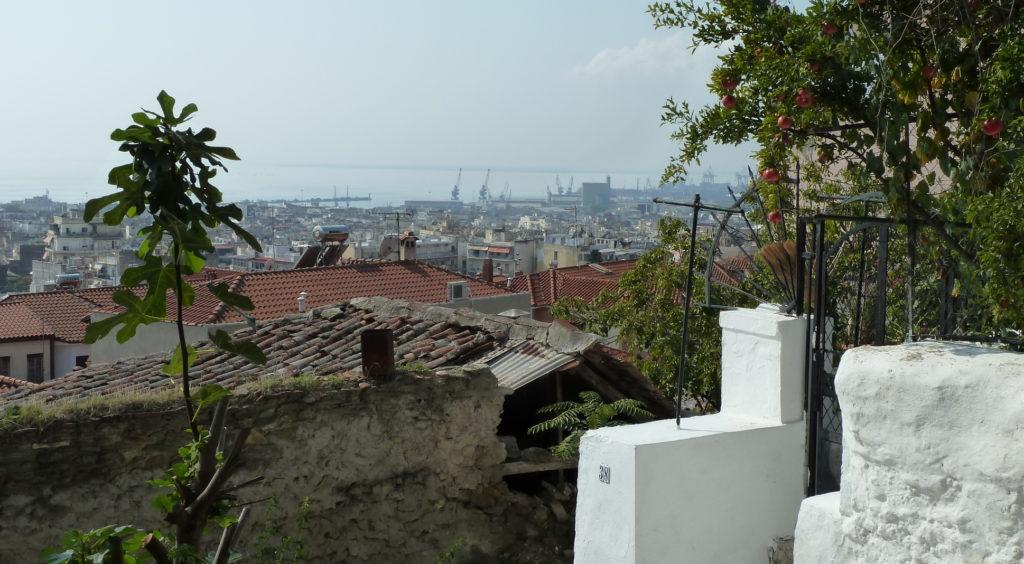 Blick über Thessaloniki von der Oberstadt aus bis zum Meer, im Vordergrund Granatäpfel und ein Feigenbäumchen