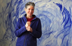 Sabine de Martin vor blau bemalter Wand