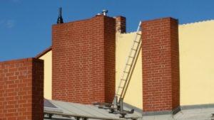 Leiter an ziegelrotem Schornstein vor gelber Wand, blauer Himmel