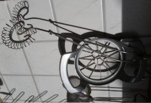 Ein Apfelteiler, ein Quirl und ein Sieb, alles metallisch glänzend, quer im Bild