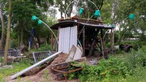 Verfallende Hütte, von verkehrten Gießkannen begossen