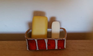 eine dicke gelbe und eine dünne weiße Seife stehend in einer rotgestreiften Seifenschale