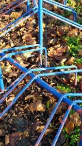 Niedrige Fahrradständer, blau, Farbe blättert ab, darunter erscheint rot, im Herbstlaub mit grünem Gras