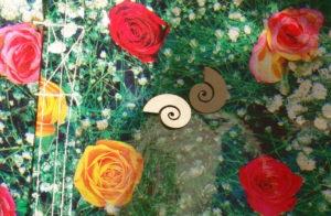 Zwei schneckenförmige Büroklammern auf einer Plastik-Blumenwiesen-Tasche