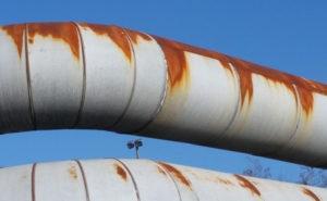 Parallele rostige Röhren vor blauem Himmel in der Kurve