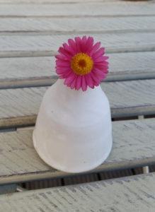 Einzelne Blume in weißer bauchiger Vase auf dem Balkon