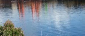 Im Wasser spiegelt sich ein Gebäude